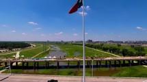 Texas flag on a flagpole flying over a bridge