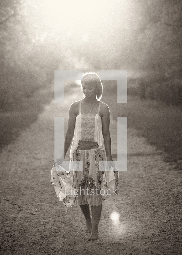 barefoot woman walking on a dirt road