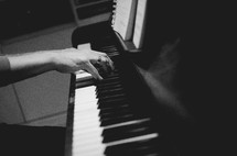a man playing a chord on a piano
