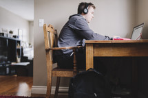 a young man reading on his laptop with headphones on