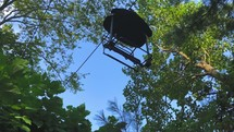 chair lift over a forest in summer