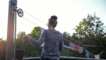 a woman putting clothes on the clothes line