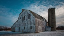 Timelapse of cloud movement over a barn and grain silo.