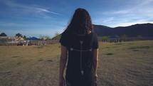 a woman walking across a field