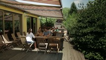 College students visiting socially on an outside, covered deck.