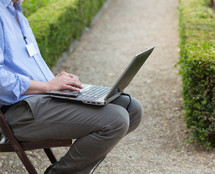 Businessman holding a laptop on his knees and looking at the laptop while sitting outdoors.