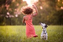 a girl dancing with her dog in a field