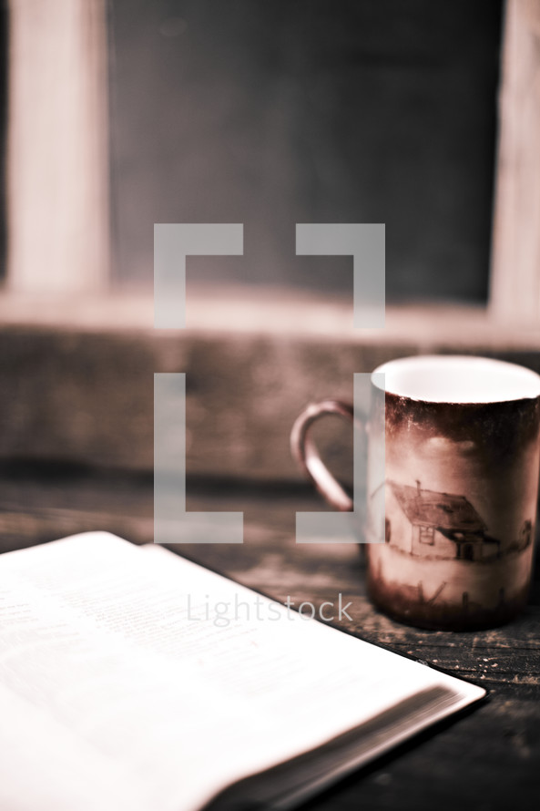 A coffee cup sits next to an open book