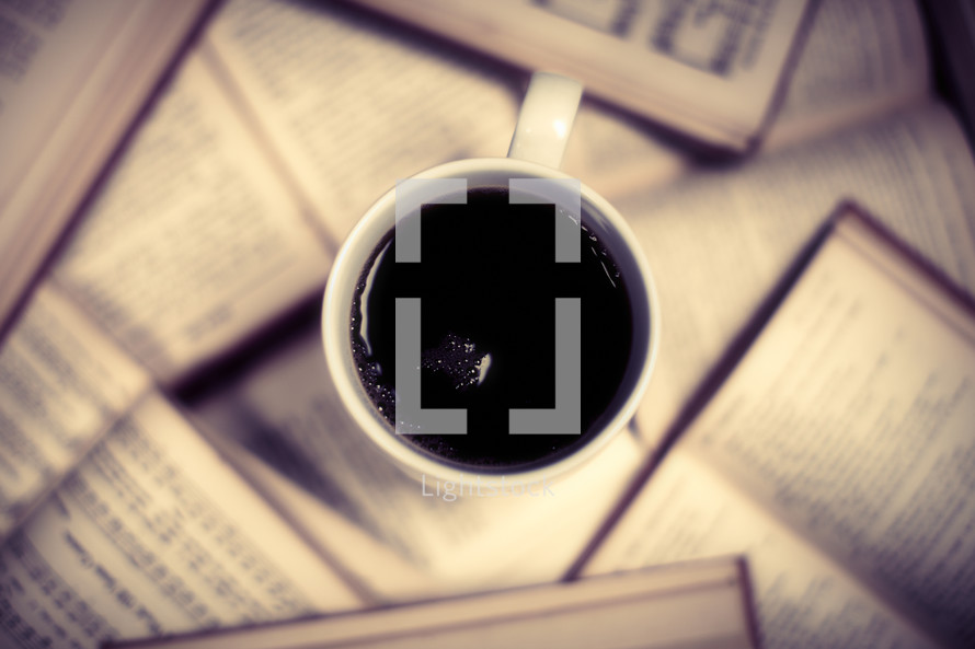 A cup of coffee rests on open books.