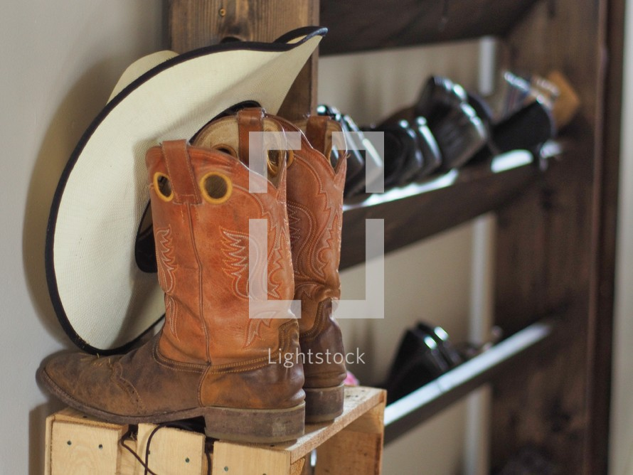 cowboy boots and cowboy hat on a shoe rack