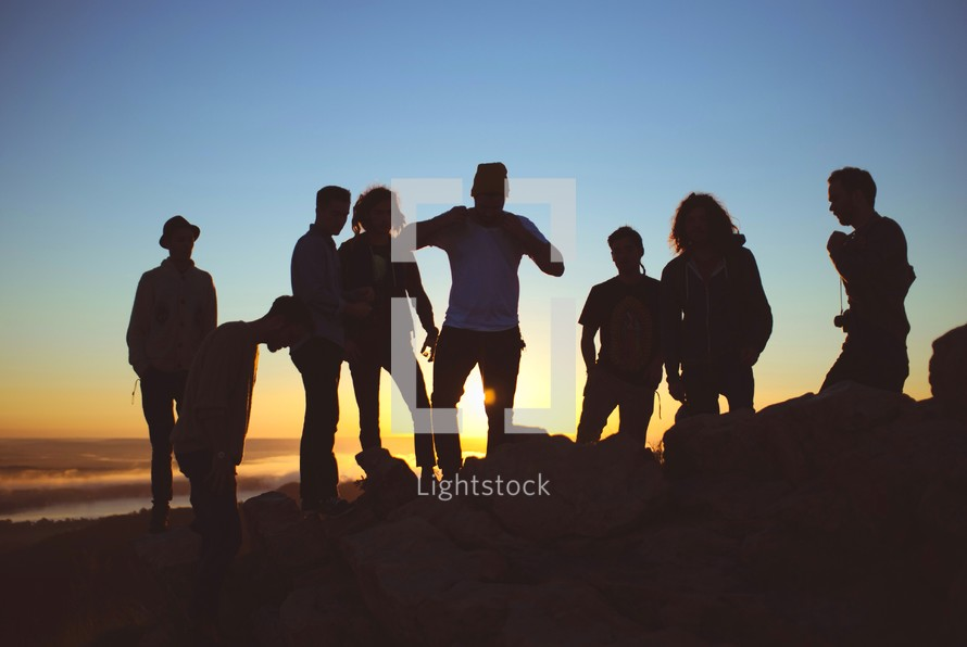 silhouette of friends on a mountain