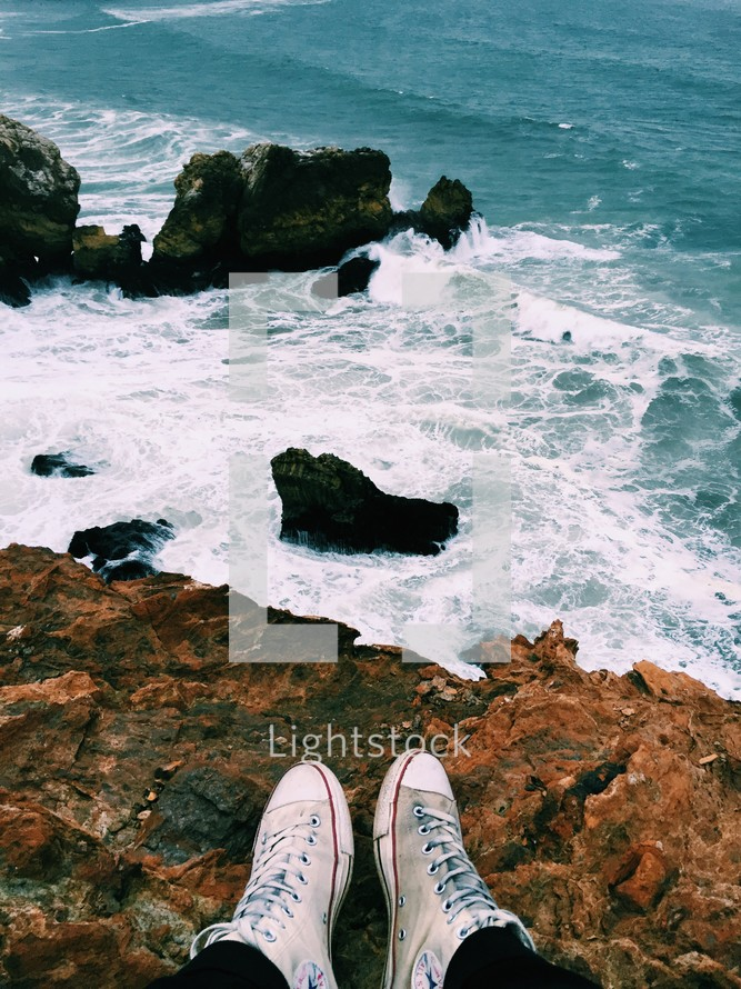 A person's feet on the edge of an oceanside cliff.