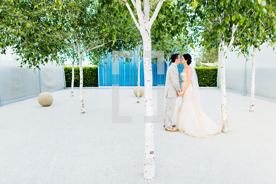 A bride and groom kissing sculpture art orchard trees blue wall wedding love dress