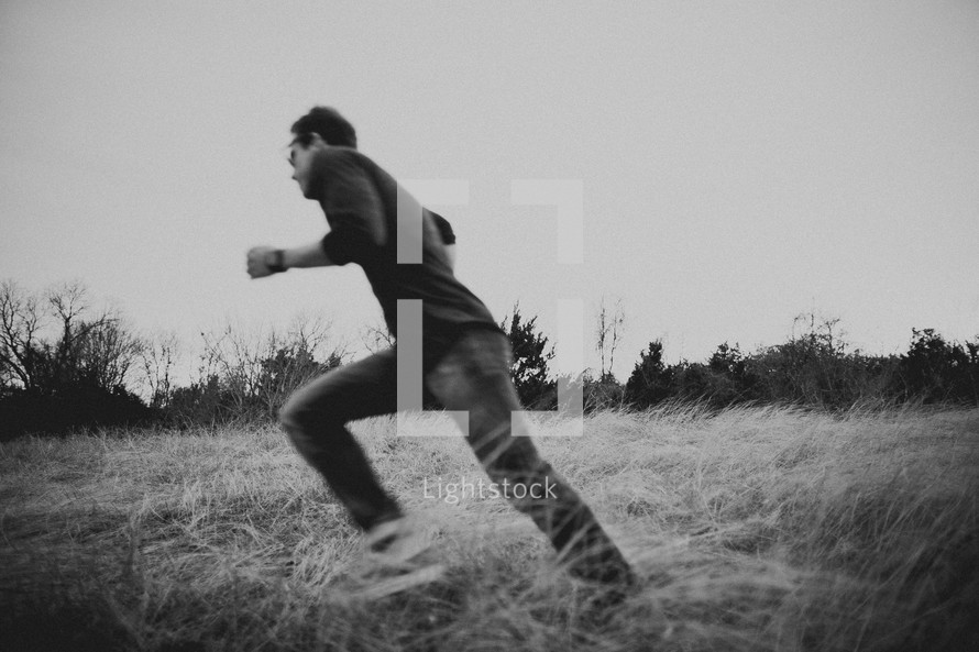 Young man running in a field surrounded by tall grass and trees.