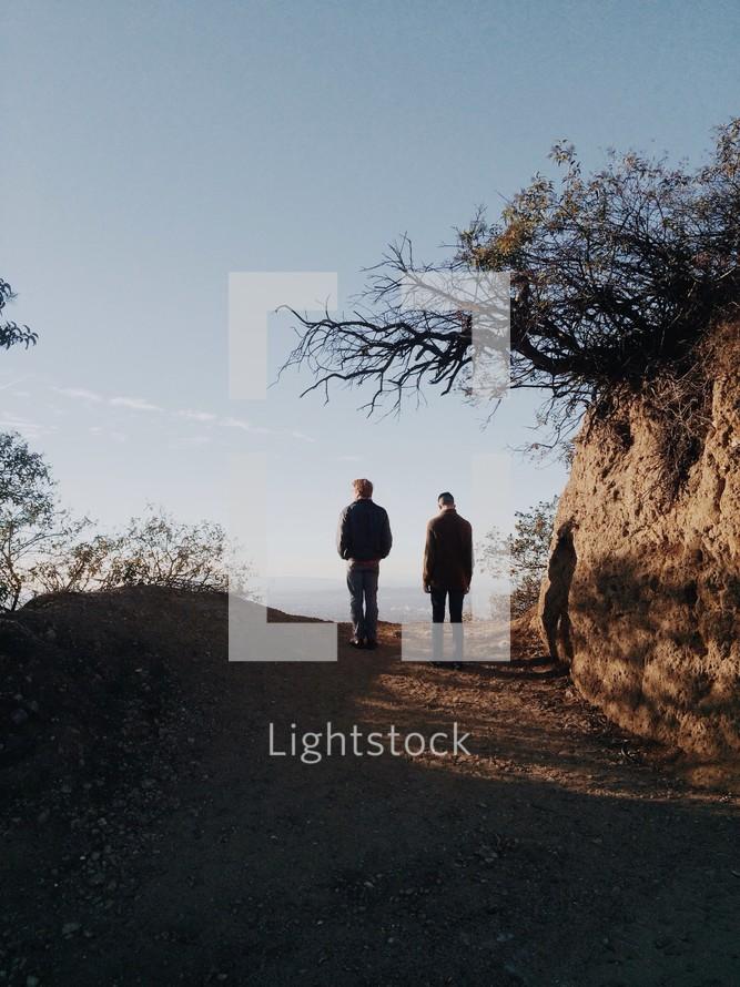 Two men walking on a dirt path.
