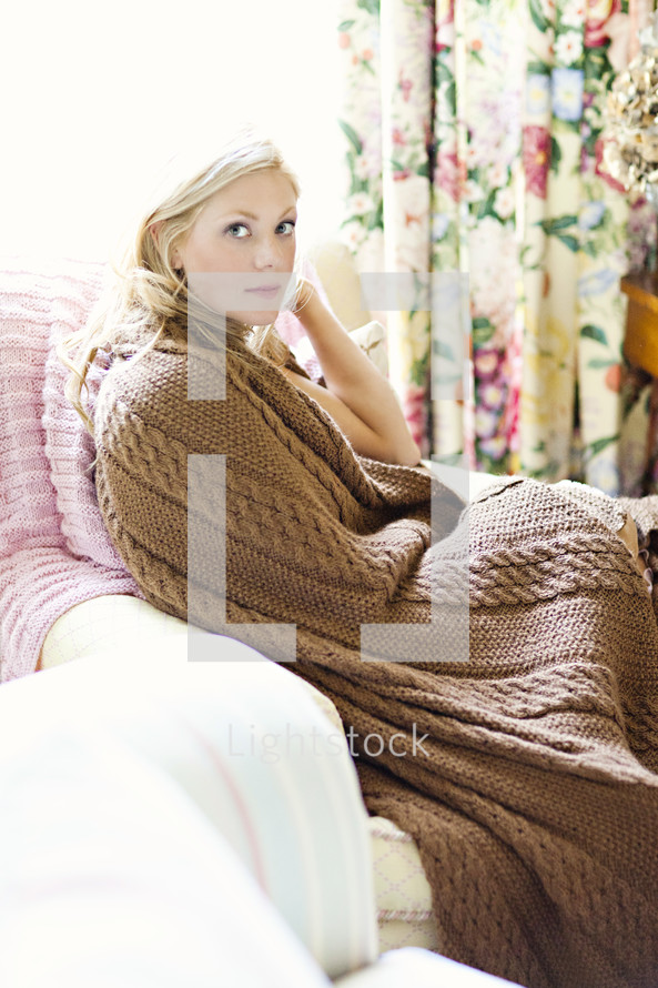 A sitting woman wrapped in a blanket.
