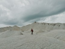 A lone man walking on a mountain of stone.