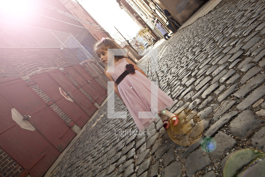 girl in a dress standing on a cobble stone street