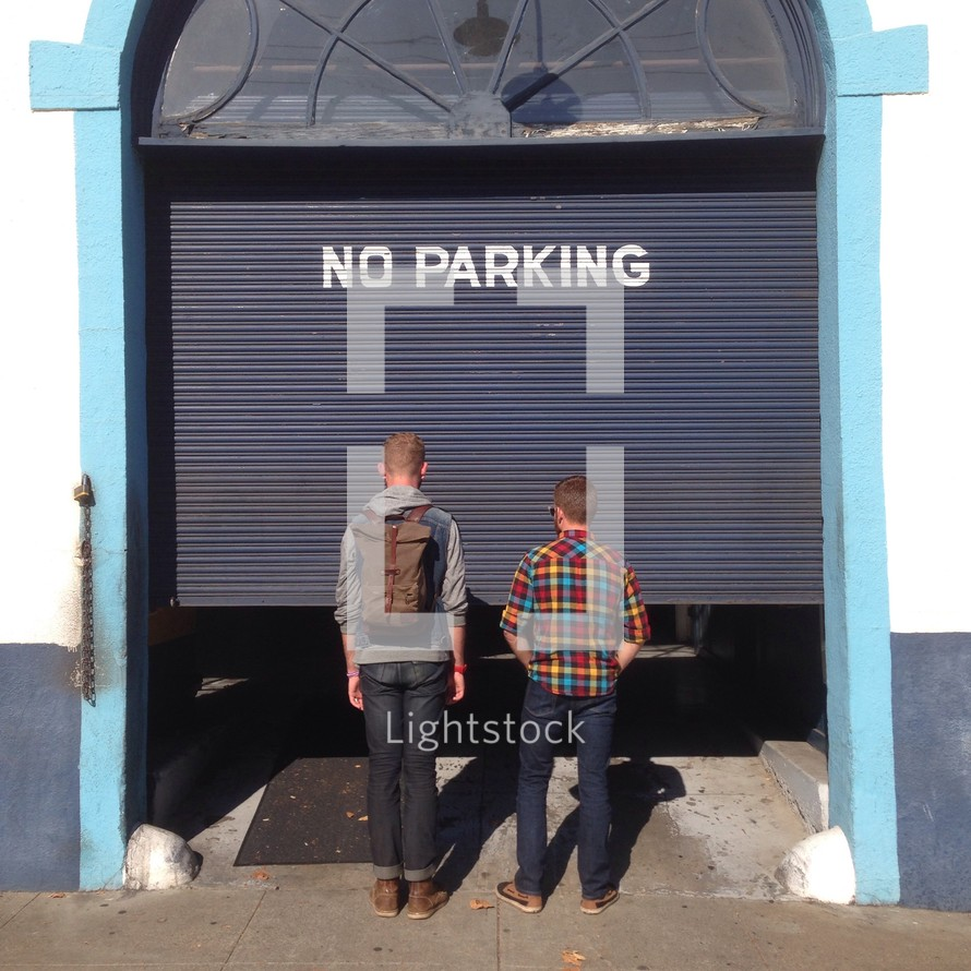 two men standing in front of a no parking sign