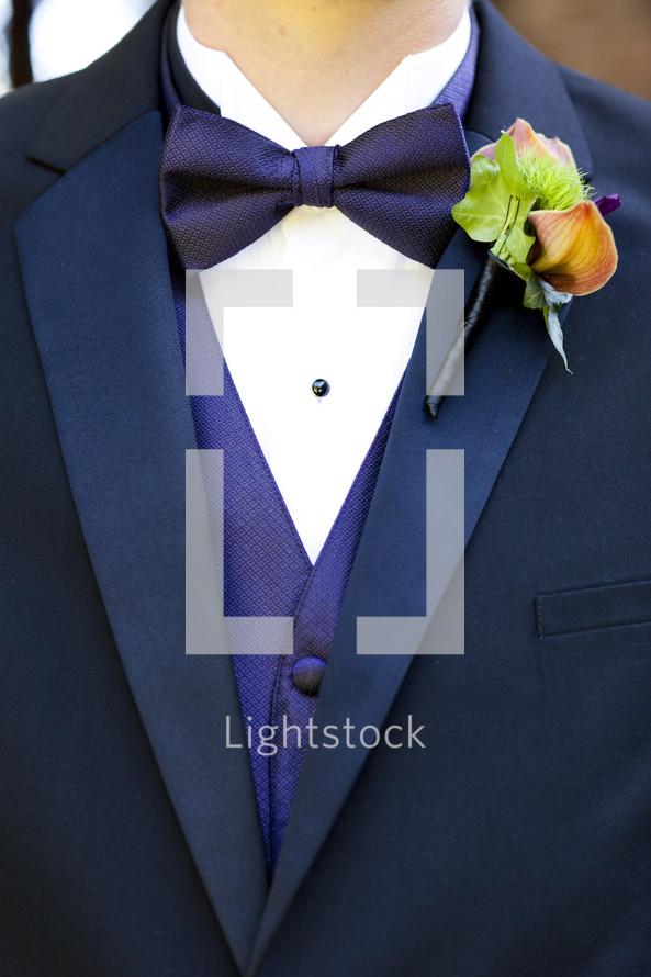 Men's tuxedo purple vest bowtie boutonniere on lapel