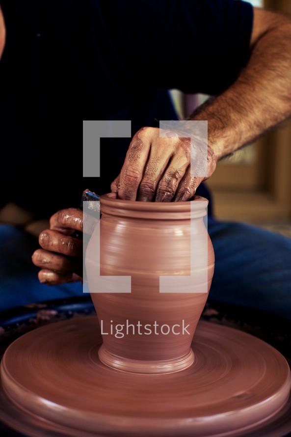 A man molding a pot on a potter's wheel
