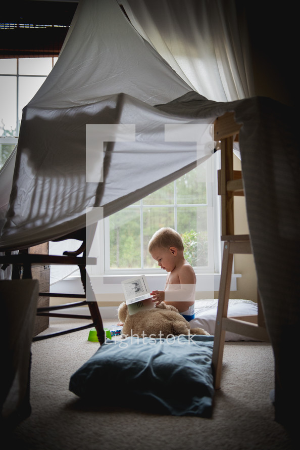 A toddler reading a book under a tent made of sheets.