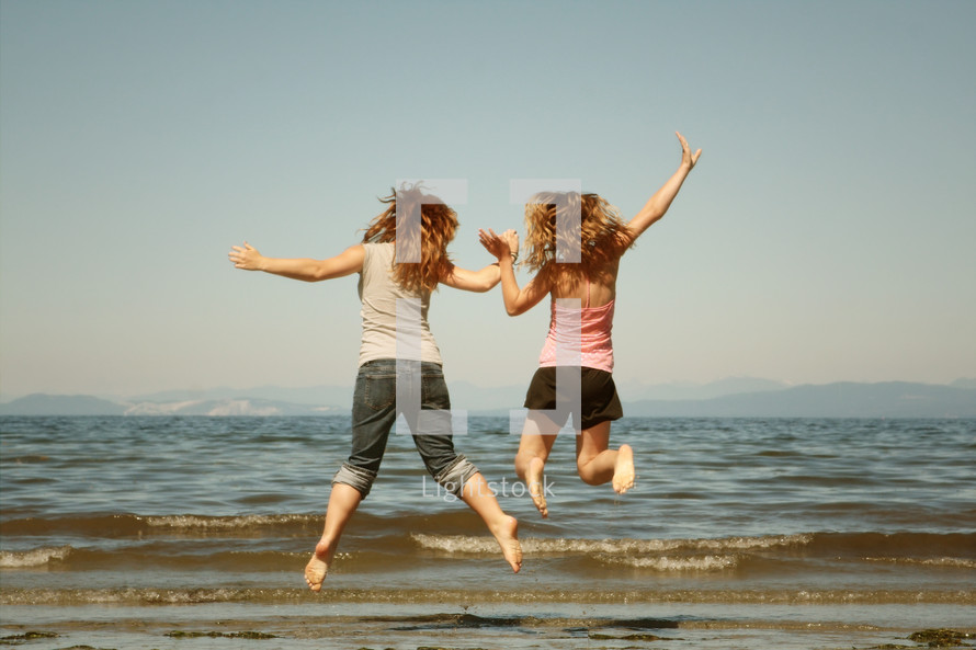 Two girls holding hands and jumping into the air on the beach.