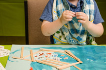 toddler with glue and paper at VBS