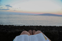Feet of a woman reading a Bible on a beach.