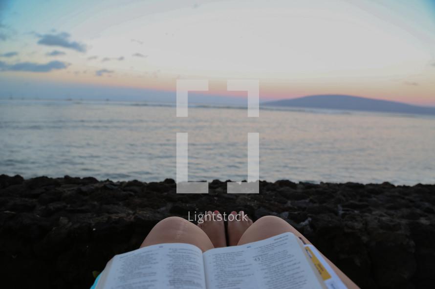 Feet of a woman reading a Bible on a beach.