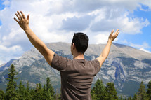 man with his hands raised in worship and praise to God in the mountains