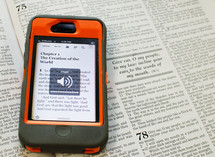Bible verse on a cellphone lying on the pages of a Bible - please silence your cell phone message for church