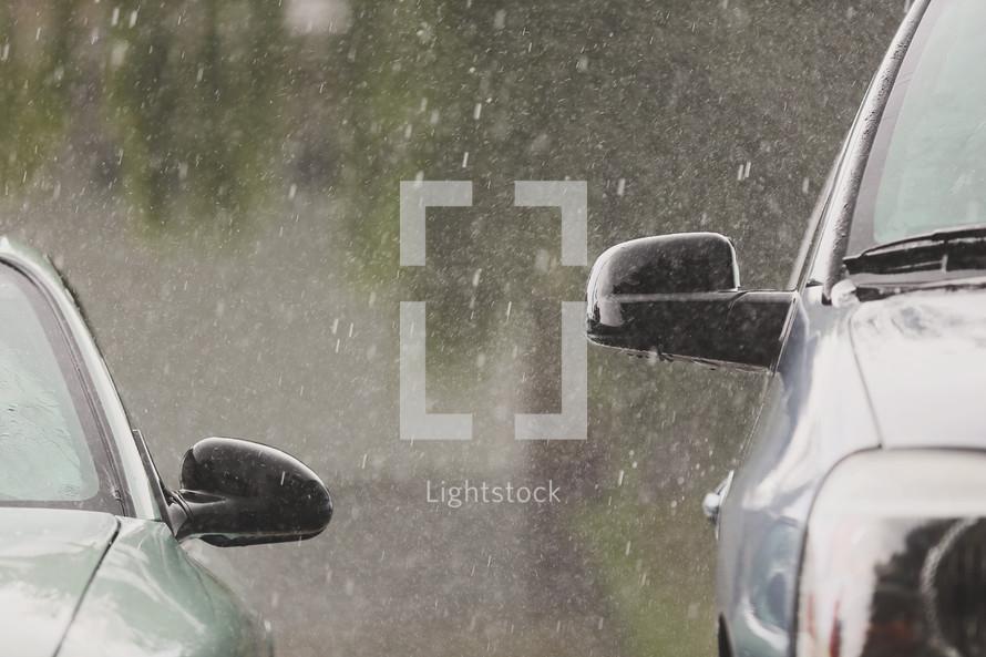 downpour of rain bounces off vehicles