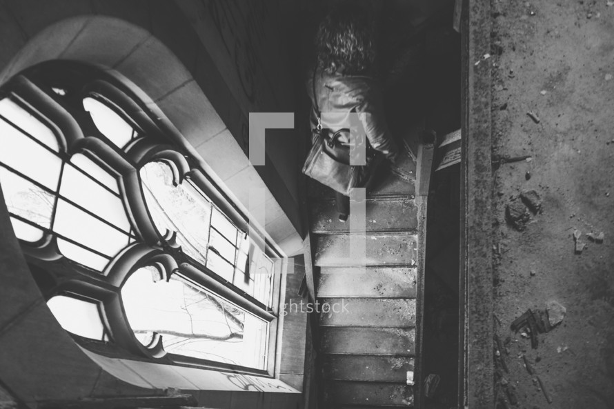 Girl walking up stairs exploring an abandoned church with stained glass window lighting the scene.
