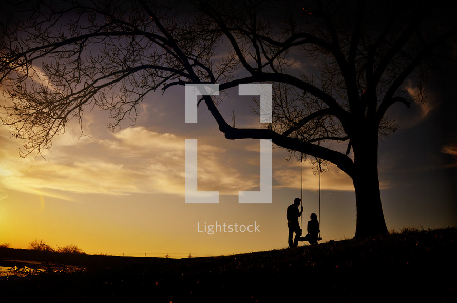 Silhouette of a couple with a tree swing at sunset.