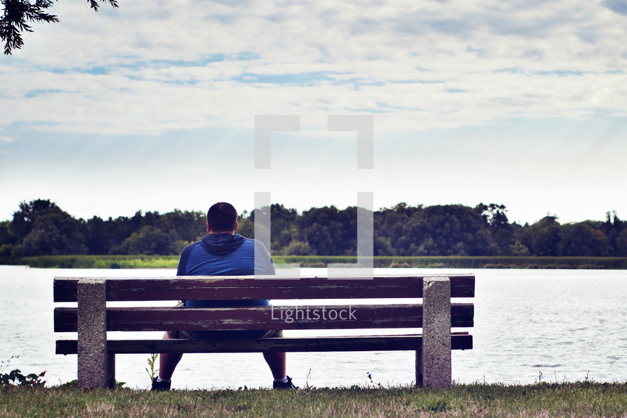man sitting on a park bench looking out over a lake