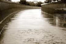 Wet sidewalk with rails.