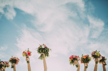 Hands holding flower bouquets toward the sky.