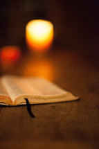 Open Bible and lit white votive candle on wooden table.