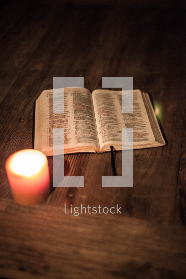 Open BIble and lit candle on wooden table.