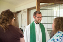 a priest greeting women in church