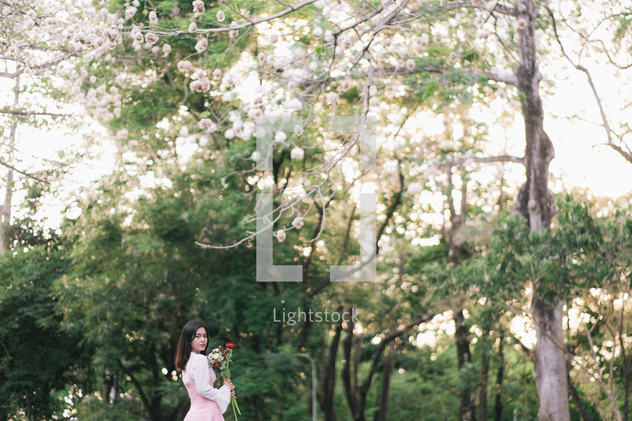 a girl holding a bouquet of flowers standing in front of spring tree