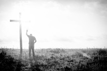 a man praying in front of a cross with raised hand