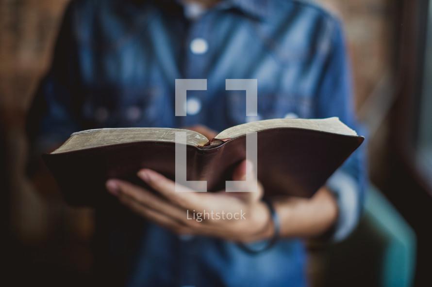 torso of a man reading a Bible