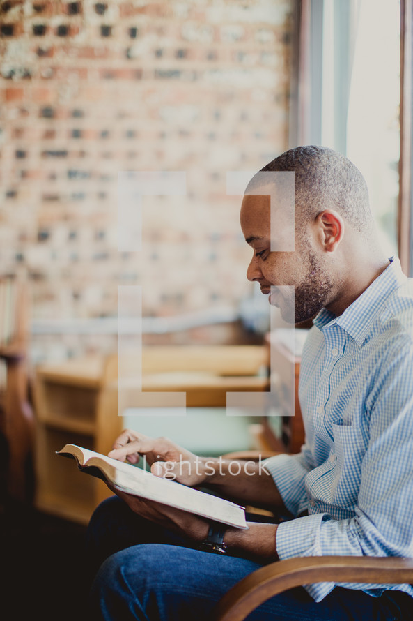 African-American man reading a Bible sitting in a chair