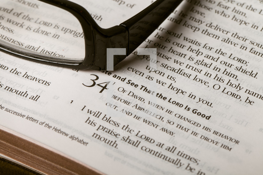 Reading glasses on top of Bible open to Psalm 34.
