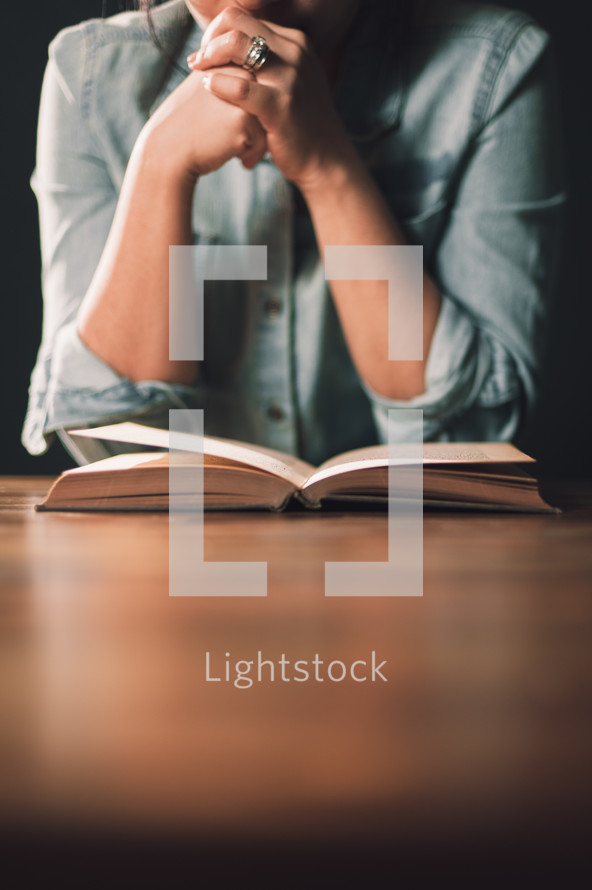woman praying over a Bible