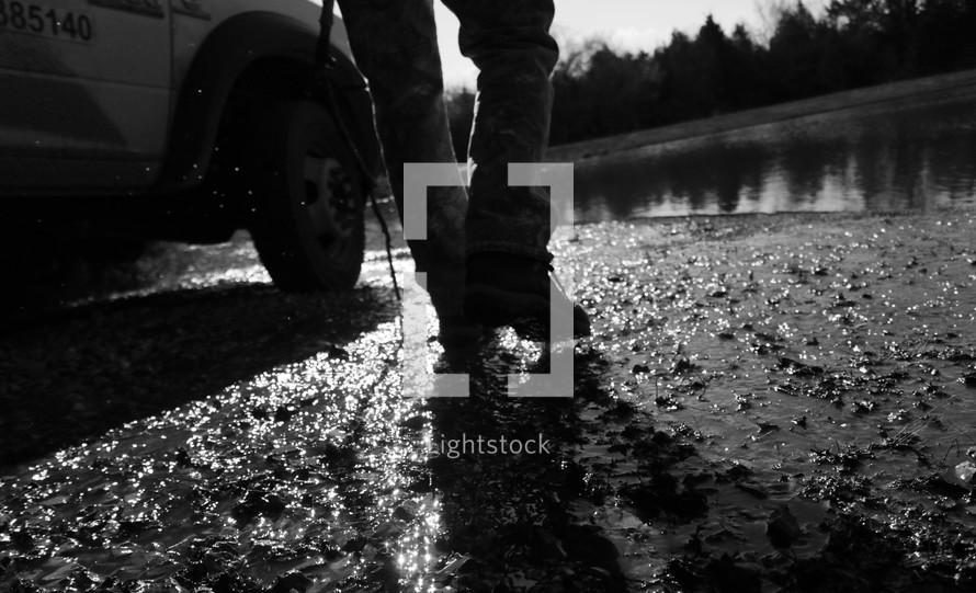 man in boots walking through mud