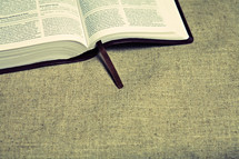 An open Bible rests on a linen table