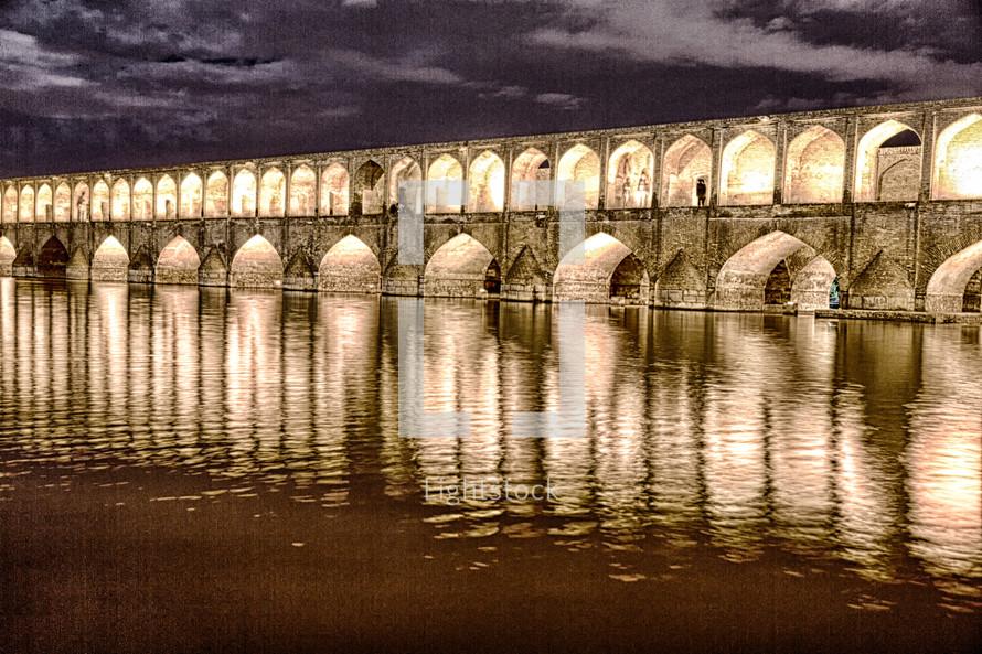 illuminate old bridge over a river